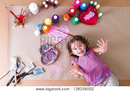 Playful Little Girl Surrounded By Her Paints