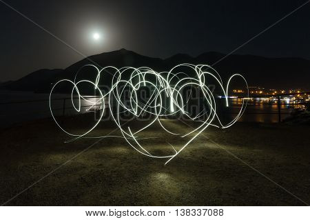 Light painting heart shapes over mountains sea and night town background. Love. Night