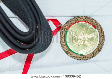 Black belt in martial arts and a part of judo uniform and medal