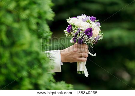beautiful wedding bouquet in hands of men.