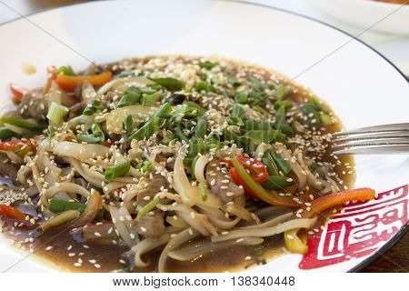 Chinese noodles with meat and vegetables and green onions in a cafe on the coast