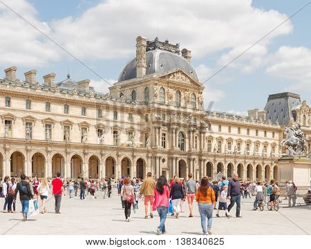 PARIS- JULY 9 : People in front of The Louvre Art Museum at sunny summer day on July 9, 2015 in Paris France