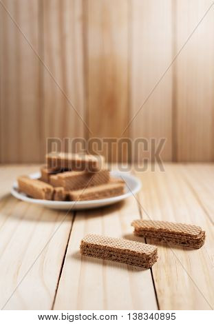 Wafers with chocolate in white plate on wooden table in still life tone