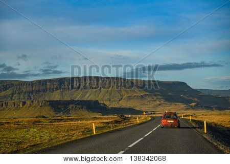 red car on the long road among beautiful scenic landscape and blue sky in summer of Iceland