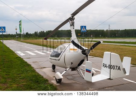 Tyumen, Russia - June 24, 2016: The 5th open championship of Russia on a plowed land. AutoGyro Europe Calidus helicopter stands on road