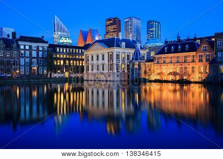 Skyline of The Hague with the modern office buildings behind the historic Mauritshuis museum and the Binnenhof parliament building next to Hofvijver lake in the Netherlands at dusk during the blue hour.