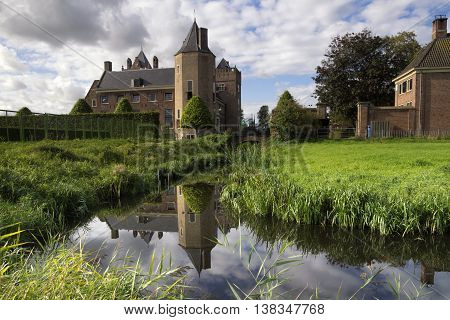 Assumburg castle in Heemskerk with its tower reflecting in the moat