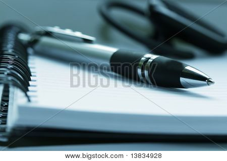 pen lying on opened  notebook