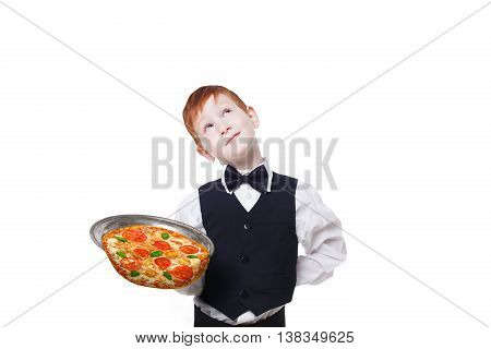 Clumsy little waiter drops tray with pizza while dreaming. Food falling down. Redhead child boy in suit shows inattentive waiter failure at white background