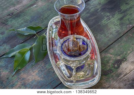 Black tea Turkish glass on a silver platter with pieces of brown sugar toned photo