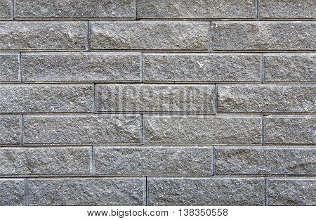 Gray rough brick wall background. Modern wall with decorative stone false bricks texture. Brickwall stucco surface