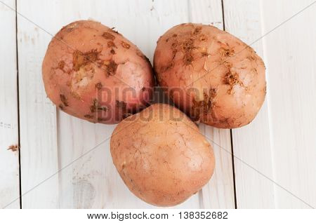 young potato tubers on a white wooden surface in a rustic style
