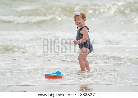 little baby girl laughing on the beach in the water. shu's playing with a toy boat. she's wearing an adorable flower swimsuit