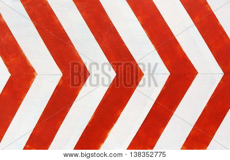 Red and white stripes closeup background. Painted concrete wall, looking like road bend traffic sign. Contrast bright lines surface.