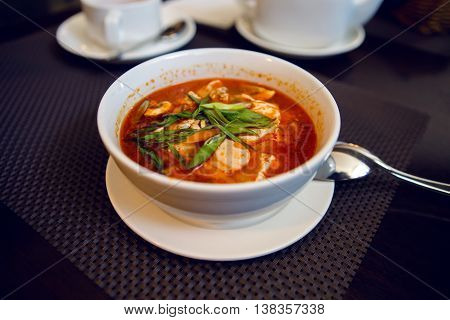 white bowl of red soup, slices of chicken and onions