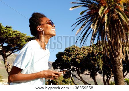 Relaxed Young Woman Listening To Music On Beach