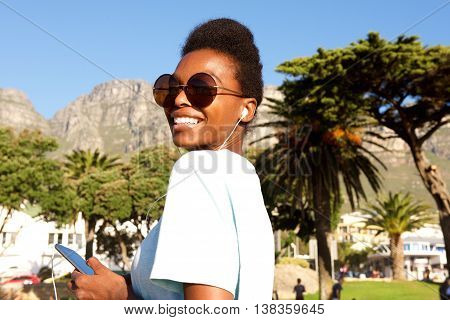 Attractive African Woman On The Beach Listening Music