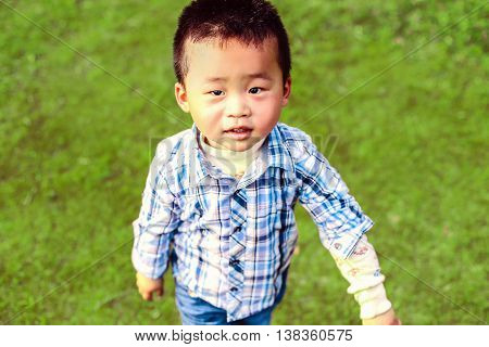 Little Chinese boy looks at the camera on a background of bright green grass.
