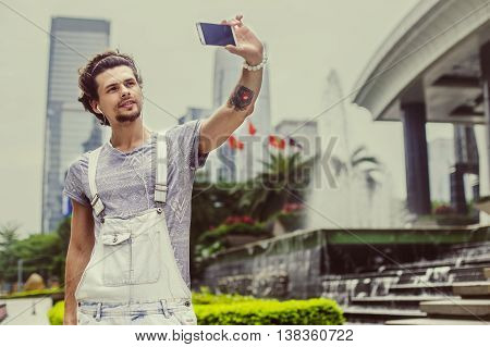 Handsome guy holding a phone and photographed himself on the background of the city.