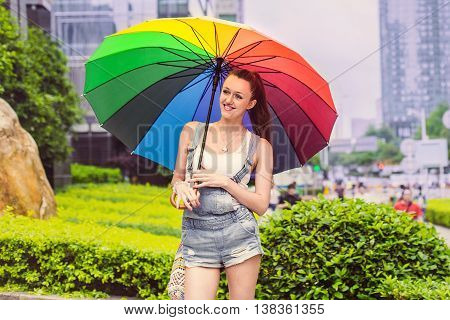 Young stylish girl standing with colored umbrella and looking to the side smiling.