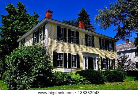 Fitzwilliam New Hampshire - July 11 2013: Handsome 18th century wooden colonial house with dual chimneys opposite the Village Green *