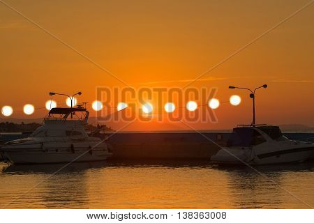 Surrealistic  view of a sunset with multiple suns hanging from the power electricity cables against the boats inside the port of Kalamos in Greece.