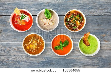Variety of restaurant hot dishes, healthy food. Japanese miso soup, asian fish soup, russian borscht, english pea soup with bacon, mushroom soup, spanish gazpacho at blue rustic wood, top view