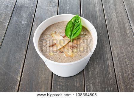 French cuisine hot food delivery - mushroom soup closeup in white plastic plate at rustic wooden background. Healthy eating concept