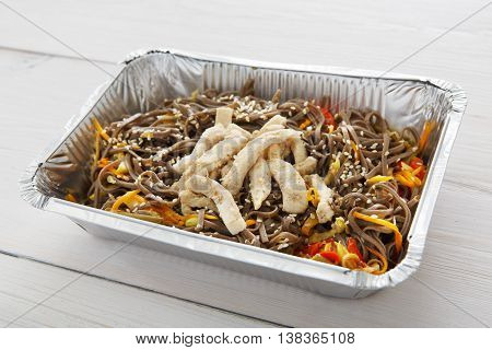 Healthy lunch and diet concept. Take away of fitness food. Weight loss nutrition in foil boxes. Brown rice vermicelli noodles with turkey meat at white wood