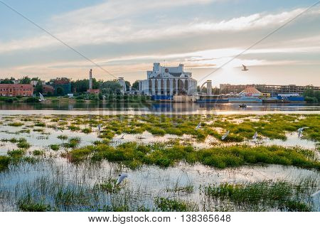 VELIKY NOVGOROD RUSSIA - JUNE 21 2016. Summer panoramic architecture view of Novgorod Regional Drama Theatre at the bank of the Volkhov river in summer evening. Picturesque architecture landscape