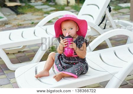little girl in a red hat sits on lounger and drinking from bottle