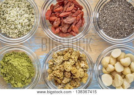 superfood abstract - hemp seeds, goji berries, chia seeds, matcha tea powder, mulberries and macadamia nuts - top view of glass bowls on wood