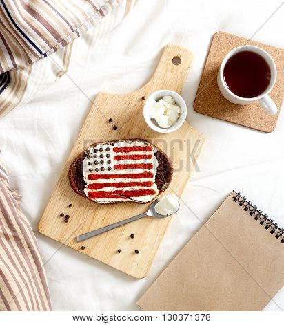 homemade sandwiches with image of american flag and quail eggs on wooden table and cup of coffe, on breakfast top view.