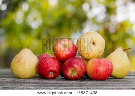 Apples and pears on wooden table over autumn bokeh background