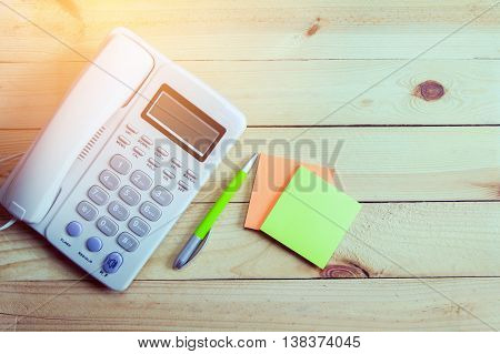 Office phone paper note and penBusiness phone and customer contact assistance concept