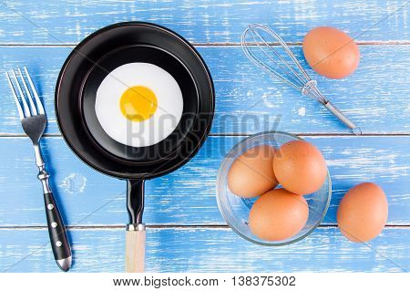 Fried Egg In Small Pan With Handle On Blue Wooden Board, Top View