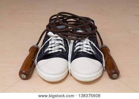 New keds with white laces and a leather skipping rope with wooden handles on a light wooden background