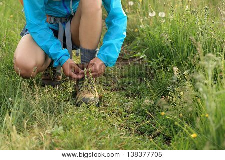 young woman hiker tying shoelace on trail in grassland