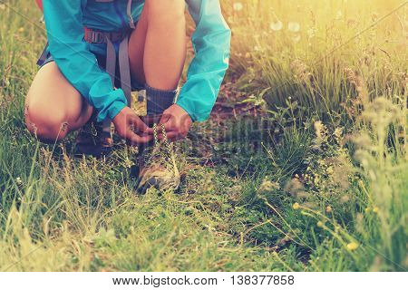 young woman hiker tying shoelace on grass trail