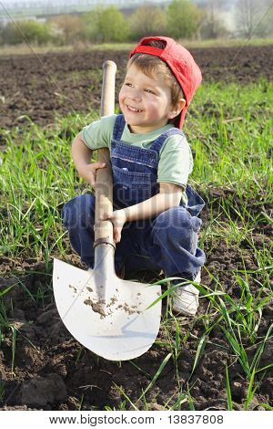 Smiling little boy sitting on field with shovel