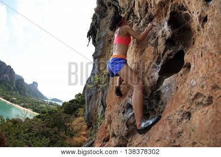 young woman rock climber climbing at seaside mountain cliff rock
