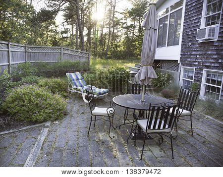 Patio with a table, chairs and umbrella in Wellfleet, MA on Cape Cod.