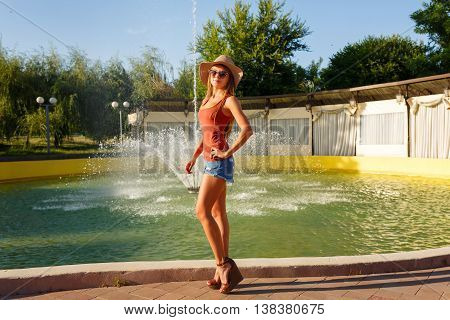Trendy girl standing near the fountain in the city park. Girl dressed in a T-shirt denim shorts a straw hat and sunglasses. On long legs girls sandals.