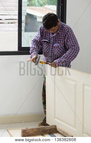 Carpenter Installer Works With Hammer And Chisel At Wood Door