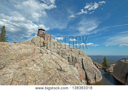 Harney Peak Fire Lookout Tower and pump house with small dam in Custer State Park in the Black Hills of South Dakota