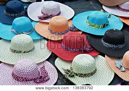 Brightly colored wide brimmed ladies straw sun hats for sale at the beachfront