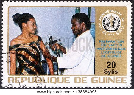 MOSCOW RUSSIA - JANUARY 2016: a post stamp printed in REPUBLIC OF GUINEA shows vaccination of a woman the series