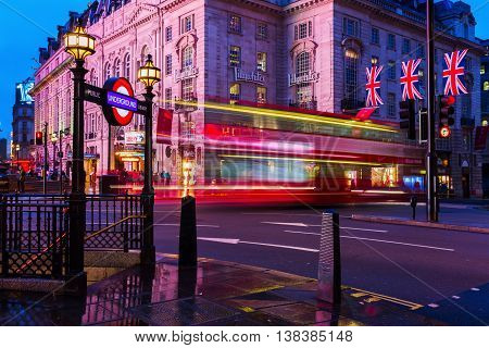 London UK - June 19 2016: red double decker bus in motion blur at Piccadilly Circus at night. Piccadilly Circus is a major traffic junction and a busy meeting place and tourist attraction.