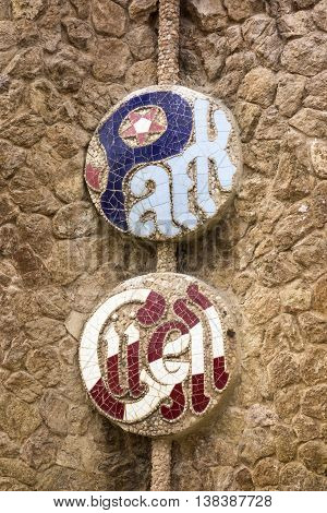 BARCELONA, SPAIN - APRIL 28 2015: An emblem for Park Guell formed out of ceramic tiles as seen on an exterior walll that surrounds the park. The park in Barcelona was designed by Antoni Gaudi.