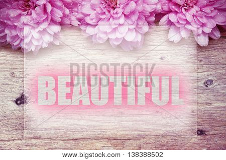 pink flowers on wooden with word BEAUTIFUL